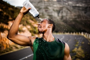 African American athlete splashing water on his face after excer