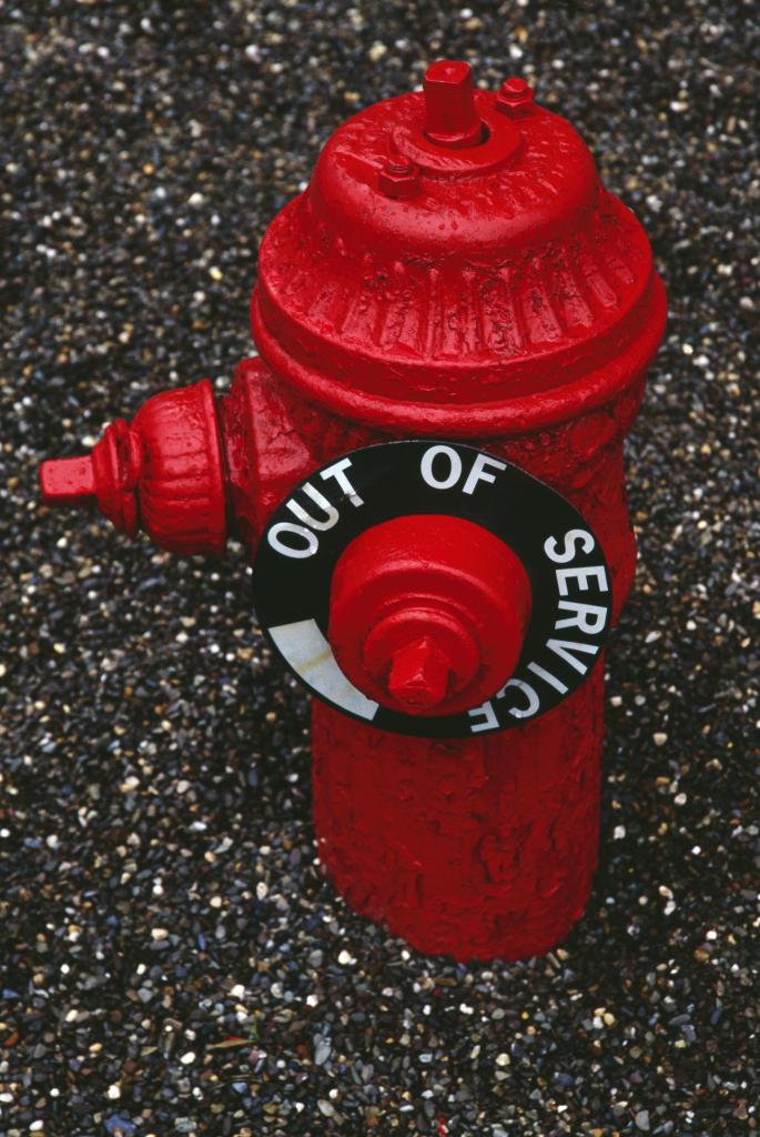 Red fire hydrant, out of service after water main break