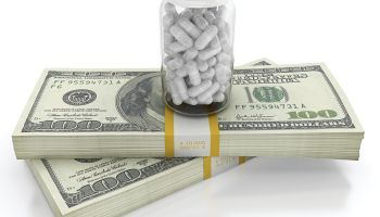 White pills on top of dollar bills bundle. High cost of healthcare concept