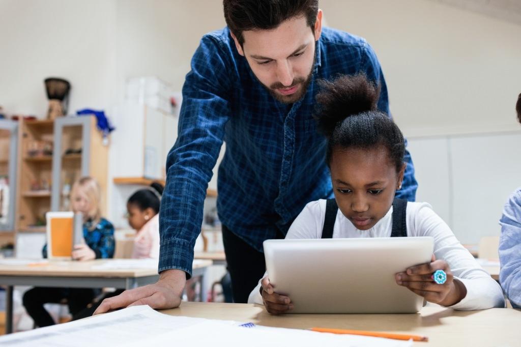 Teacher looking at girl using digital tablet in classroom