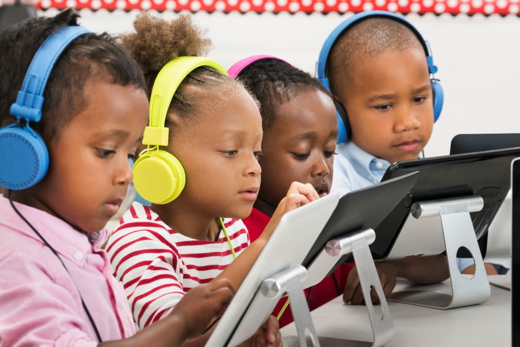 Students using digital tablets with headphones in classroom