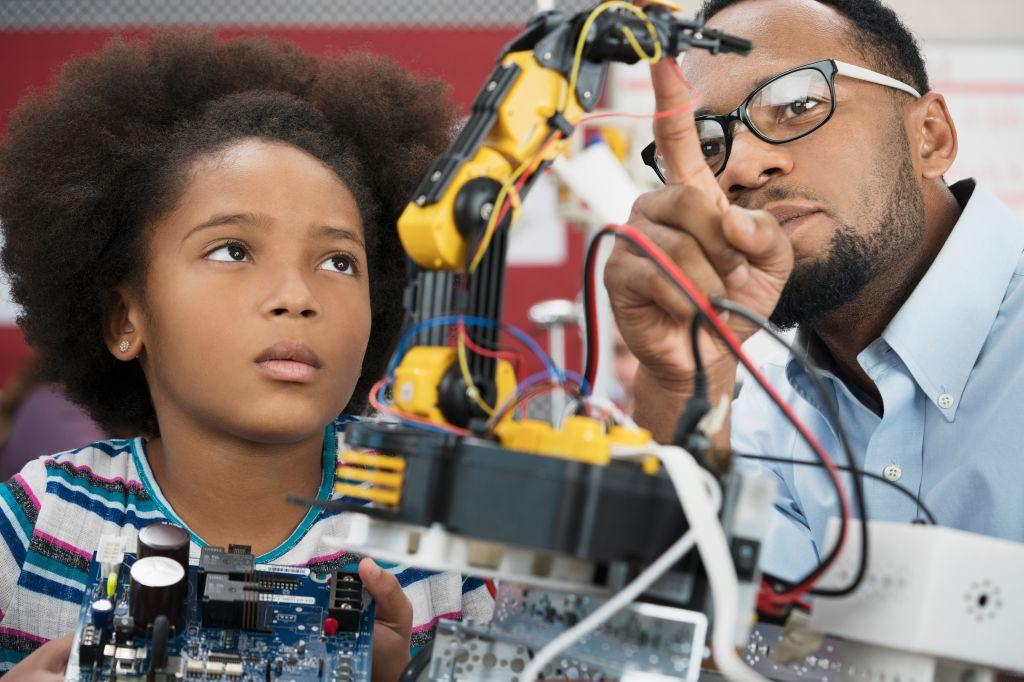 Black teacher helping student with robotics