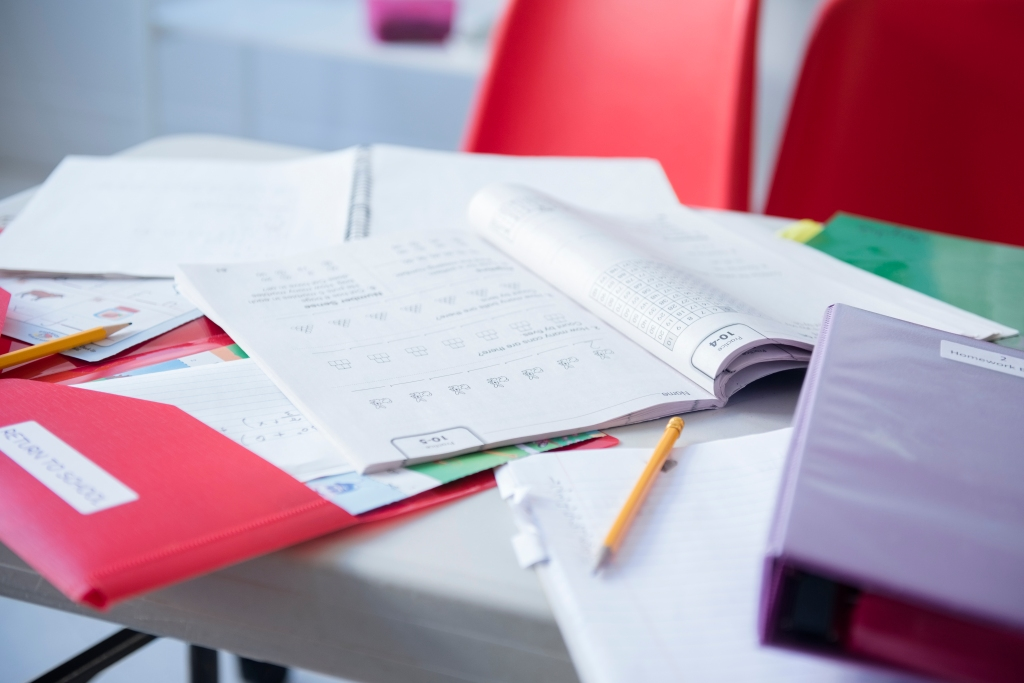 Workbook and folder on desk in classroom