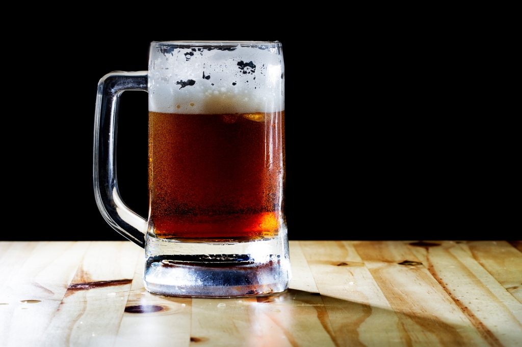 selective focus dark beer and foam with Beer mug and soft flare filter