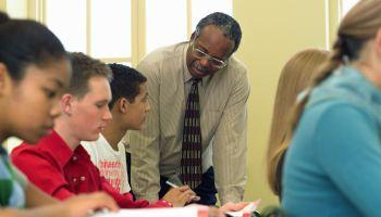 Teacher leaning over students desk, high school classroom