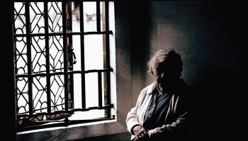 An elderly woman enjoys the sunlight from a window, 4 April 1996. AFR Picture b