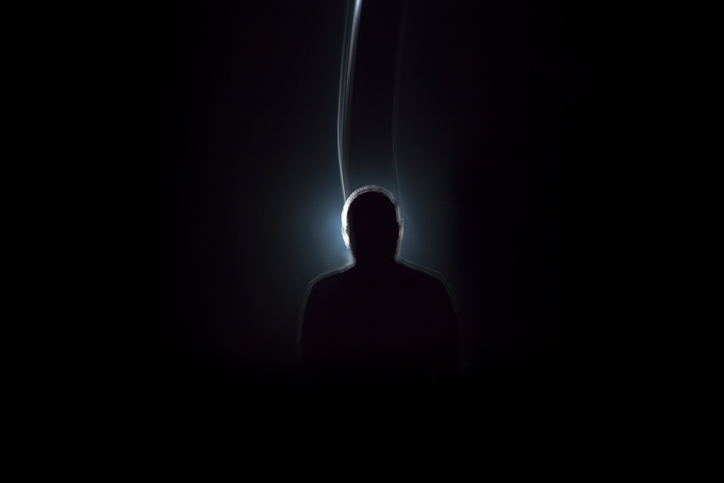 Silhouette of man in dark tunnel