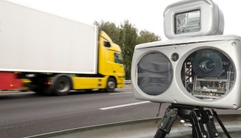 Speed Camera Against Blurred Motion Of Truck On Road
