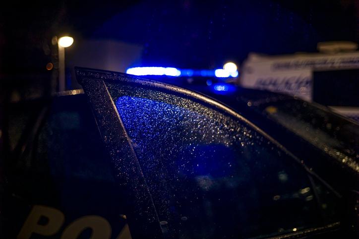 Spain, Madrid, rain falling on the window of police car at night