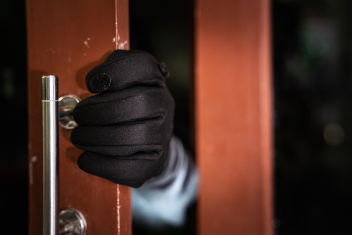 dangerous masked burglar with crowbar breaking into a victim's home door,Home insurance concept